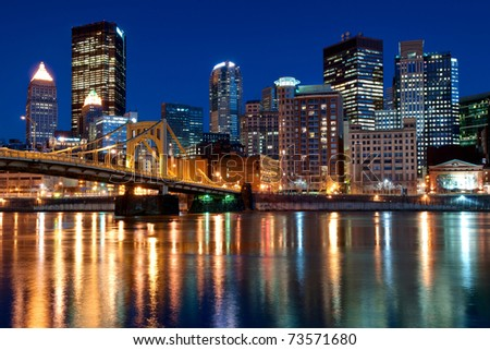 A view of the Pittsburgh, Pennsylvania cityscape at night overlooking the Allegheny River with a view of the Andy Warhol Bridge. - stock photo