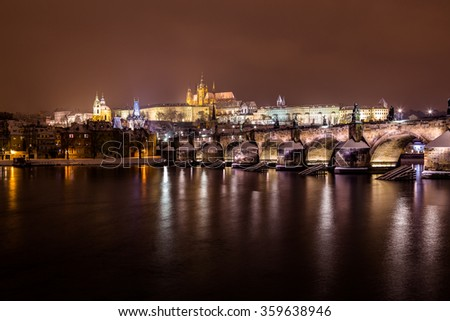 A view of the Prague Skyline towards the Lesser Quarter (Lesser Town) at night during the winter. Reflections can be seen in the River Vltava - stock photo