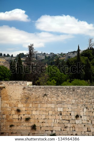 A view of the Wailing Wall in the old city of Jerusalem and the trees &buildings (and one church) behind it. - stock photo