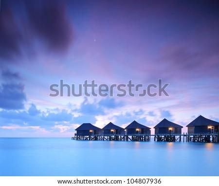 A view of water villa cottages at sunset on island of Kuredu, Maldives, Lhaviyani atoll - stock photo