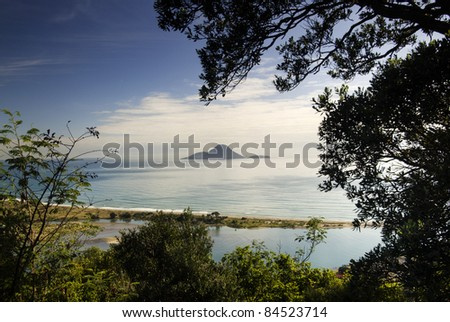 A view of Whale Island ( Moutohora ), Whakatane, North Island, New Zealand. Blue sky, sunny day. - stock photo