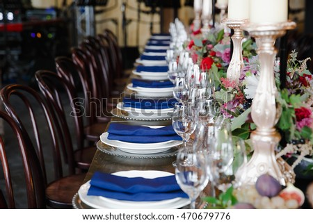 A view on a aristocratic served dinner table with blue serviettes on the plates