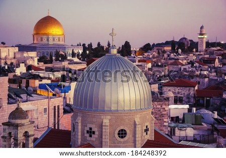 A view on n rooftops of Old City of Jerusalem at sunset. Grey dome of Church of Our Lady of the Spasm (Armenian church) and golden Dome of the Rock.