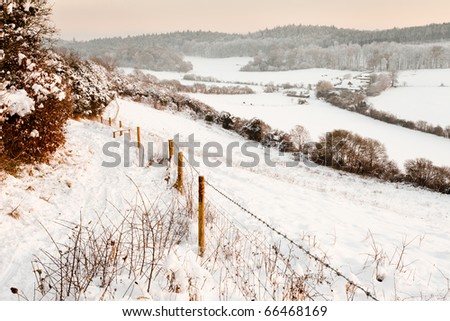 A view over some snow covered fields at dusk.  Taken on Pewley Down in Guildford, Surrey on a snowy December evening. - stock photo