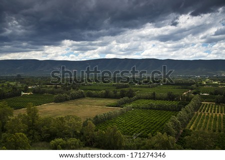 A view over the farmlands on a dark overcast day - stock photo