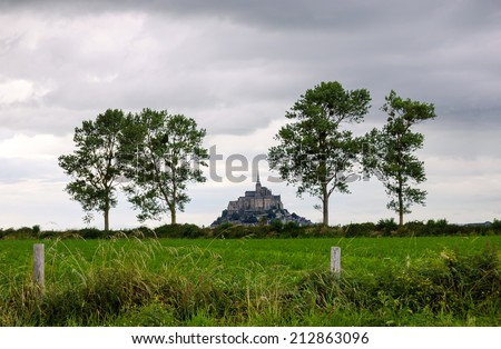 A view through the field and the trees on Mont Saint Michel UNESCO heritage site. Cloudy evening. Normandy, France. Selective focus on the Mont Saint Michel. - stock photo
