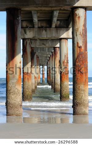 A view under a long, tall pier and the rusted pilings supporting it.  Taken in the late afternoon sun with deep shadows. - stock photo