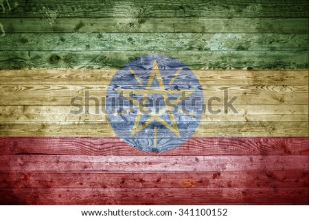 A vignetted background image of the flag of Ethiopia painted onto wooden boards of a wall or floor. - stock photo