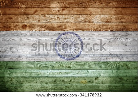 A vignetted background image of the flag of India painted onto wooden boards of a wall or floor. - stock photo