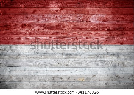 A vignetted background image of the flag of Indonesia painted onto wooden boards of a wall or floor. - stock photo