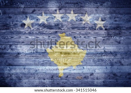 A vignetted background image of the flag of Kosovo painted onto wooden boards of a wall or floor. - stock photo