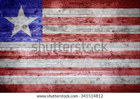 A vignetted background image of the flag of Liberia painted onto wooden boards of a wall or floor. - stock photo