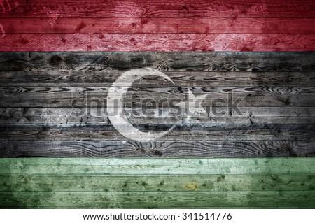 A vignetted background image of the flag of Libya painted onto wooden boards of a wall or floor. - stock photo