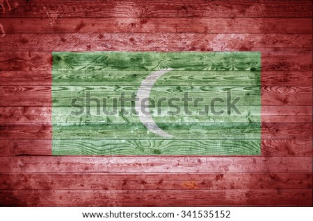 A vignetted background image of the flag of Maldives painted onto wooden boards of a wall or floor. - stock photo