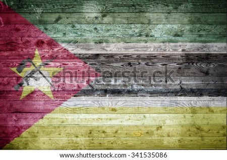 A vignetted background image of the flag of Mozambique painted onto wooden boards of a wall or floor. - stock photo
