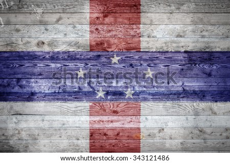 A vignetted background image of the flag of Netherlands Antilles painted onto wooden boards of a wall or floor. - stock photo