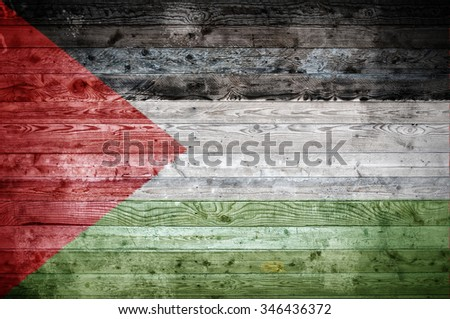 A vignetted background image of the flag of Palestine onto wooden boards of a wall or floor. - stock photo