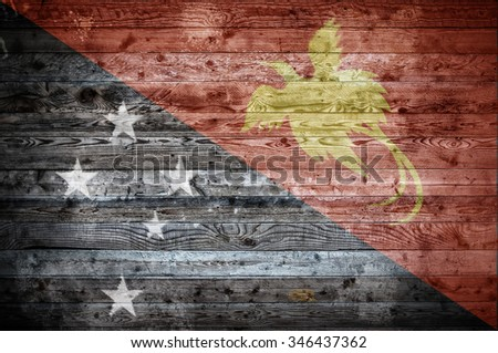 A vignetted background image of the flag of Papua New Guinea onto wooden boards of a wall or floor. - stock photo