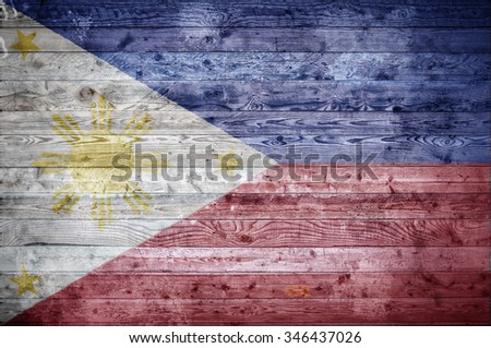 A vignetted background image of the flag of Philippines onto wooden boards of a wall or floor. - stock photo