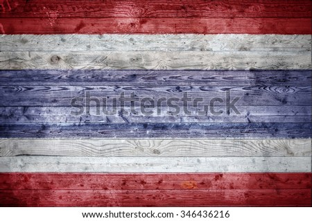 A vignetted background image of the flag of Thailand onto wooden boards of a wall or floor. - stock photo