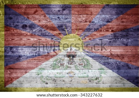 A vignetted background image of the flag of Tibet onto wooden boards of a wall or floor. - stock photo