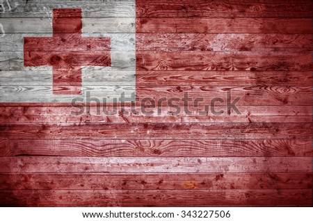 A vignetted background image of the flag of Tonga onto wooden boards of a wall or floor. - stock photo