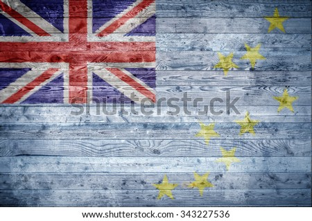 A vignetted background image of the flag of Tuvalu onto wooden boards of a wall or floor. - stock photo