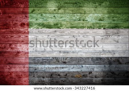 A vignetted background image of the flag of United Arab Emirates onto wooden boards of a wall or floor. - stock photo
