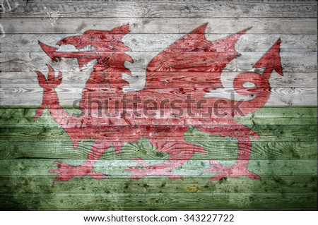 A vignetted background image of the flag of Wales onto wooden boards of a wall or floor. - stock photo