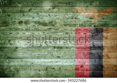 A vignetted background image of the flag of Zambia onto wooden boards of a wall or floor. - stock photo