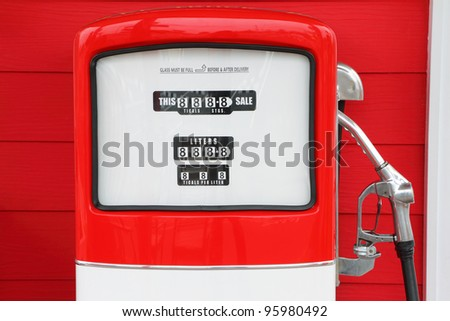 A vintage antique Gasoline fuel pump on red background - stock photo