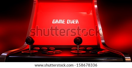 A vintage arcade game machine with a bright red illuminated screen that reads game over in white on a dark arcade background - stock photo