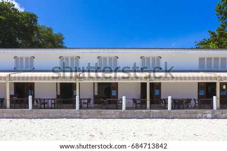 A vintage beach restaurant on the popular vacation island of Mahé in the Seychelles with a blue sky and trees to the side.