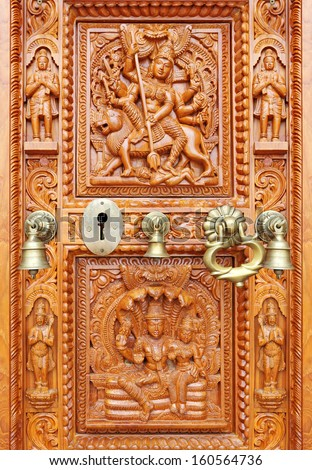 A vintage brass keyhole and religious ornament on an old exotic brown ornate Hindu temple door.  - stock photo