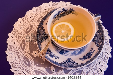 A vintage china teacup holds thirst-quenching tea with lemon for an afternoon refresher. - stock photo