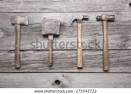 A vintage hatchet, mallet, claw hammer and ball-peen hammer sit on a rustic wooden background. - stock photo
