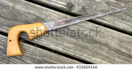 A vintage key hole saw on a wood background - stock photo