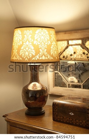 A vintage lamp on a table with decorations in the corner - stock photo