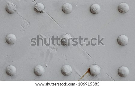 A vintage metal plate with rivets for textural background.