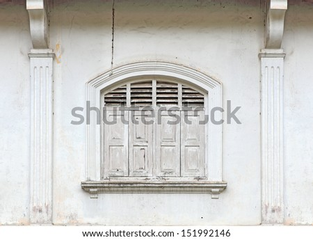 A vintage old ornate window on a weathered building wall.  - stock photo