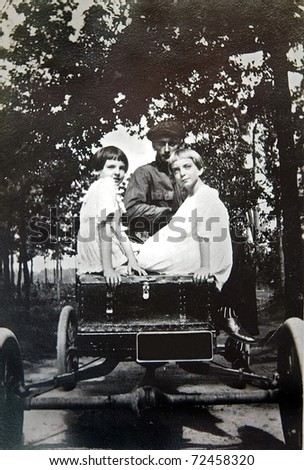 A vintage photo of two girls and a man in an automobile.  It is on textured paper and shows signs of wear.