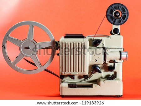 A vintage retro movie projector on a red background - stock photo