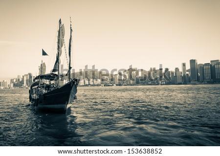 A vintage shot of a traditional junk ship sailing along Victoria Harbor in Hong Kong. - stock photo