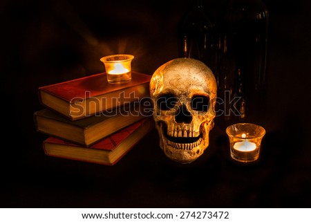 A vintage skull sits beside a stack of old novels and wine bottles; image created with a light painting technique - stock photo