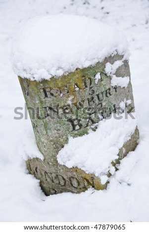 A vintage stone carved British milestone road sign covered in winter snow and showing distances to London, Reading, Newbury and Bath - stock photo
