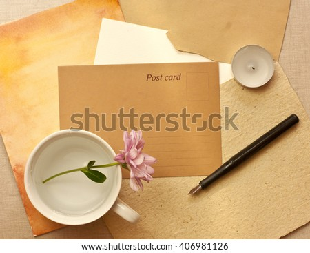 A vintage style still life with a brown paper postcard with a place for text, a tender pink chrysanthemum in a white cup, an ink pen, a candle, and some old paper textures - stock photo
