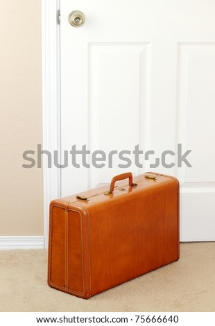 A vintage suitcase by the door