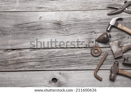 A vintage tool border on a rustic background of grey barn board. - stock photo