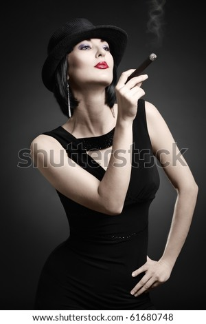 A vintage woman smoking a cigar isolated on dark background - stock photo