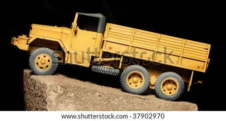 A Vintage Yellow Truck on Black Background - plastic kit 1:48 scale - close up - stock photo
